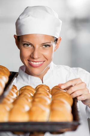 panino: Portrait of beautiful woman with freshly baked breads in bakery
