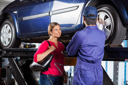 Happy female customer looking at mechanic refilling car tire at garage Foto de archivo