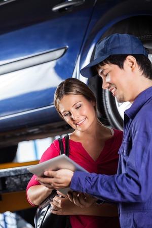 mecanico: Mecánico de sexo masculino feliz que usa la tableta digital con el cliente femenino en el garaje Foto de archivo