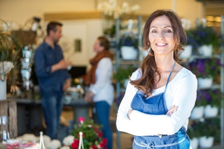 Portrait of smiling mid adult florist with customers in background at flower shop Standard-Bild