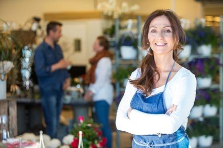 Retrato de la sonrisa mediados floristería adulto con clientes en segundo plano en la tienda de flores Foto de archivo