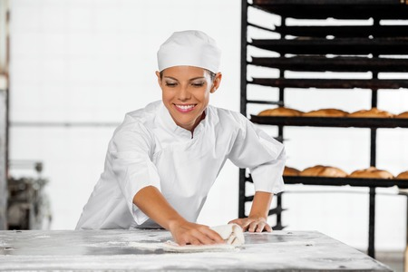 work table: Beautiful smiling baker cleaning flour from table in bakery