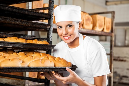 gourmet: Portrait of confident female baker holding baking tray by rack in bakery