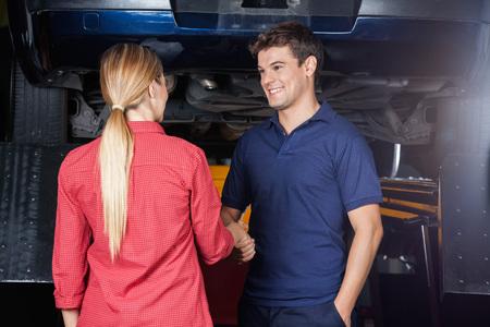 Lachende man monteur schudden hand met de klant bij auto reparatiewerkplaats