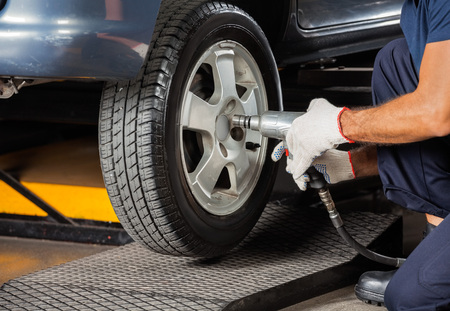 screwing: Low section of male technician screwing car tire with pneumatic wrench at garage