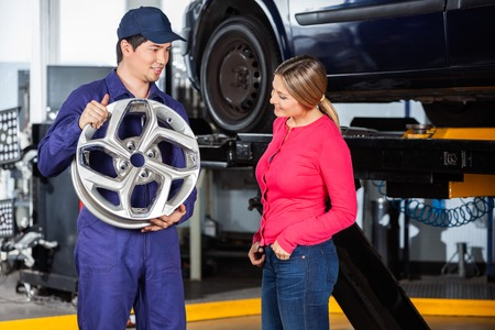 hubcap: Male mechanic showing metallic hubcap to female customer at garage