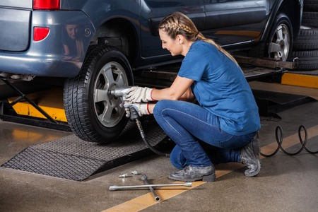 auto repair: Female mechanic fixing car tire with pneumatic wrench at auto repair shop Stock Photo