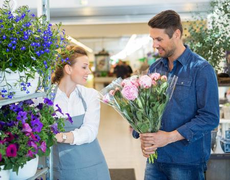 Fiorista assistere cliente maschio ad acquistare bouquet di fiori in negozio photo
