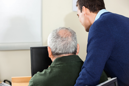 the elderly tutor: Side view of young male teacher assisting senior man in computer class Stock Photo