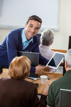 the elderly tutor: Portrait of confident teacher showing digital tablet to senior students at desk in computer class Stock Photo