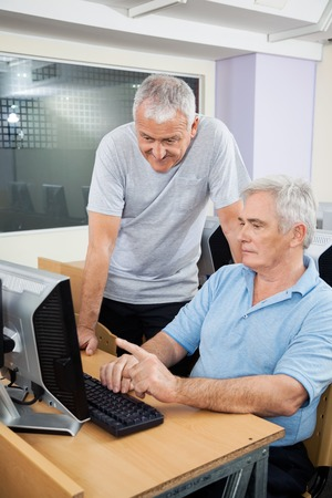 classmate: Senior man with classmate using computer at desk in classroom Stock Photo