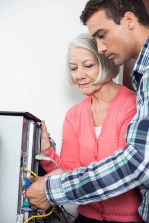 the elderly tutor: Male tutor assisting senior woman setting up computer in classroom