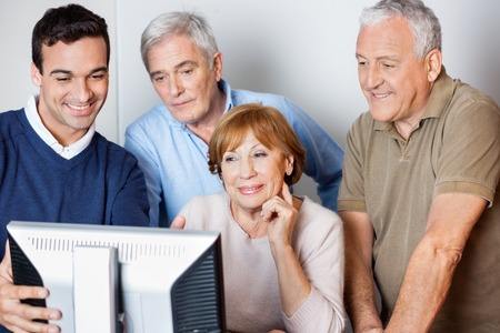 the elderly tutor: Male teacher assisting senior people in using computer at class