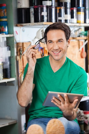 lavoratore di sesso maschile premurosa che tiene occhiali e computer tablet in cartiera photo