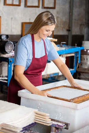 Happy female worker dipping mold in pulp and water mixture at paper factory Stock Photo