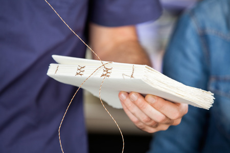 Cropped image of male worker binding pages in paper factory