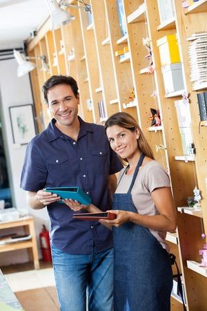 Ritratto di sorridere Saleswoman che mostra i libri di cliente maschio in negozio photo