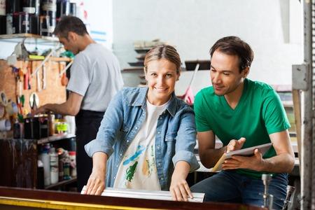 Ritratto di metà lavoratore adulto utilizzando seccatoio mentre supervisore tenendo tavoletta digitale in cartiera photo