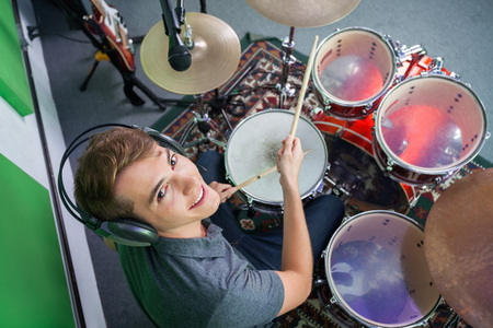 High angle portrait of smiling male drummer wearing headphones while performing in recording studio