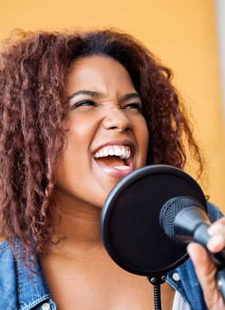 frizzy: Closeup of young woman with frizzy hair singing while looking away in recording studio