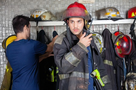 walkie talkie: Male firefighter using walkie talkie at fire station with colleague in background Stock Photo