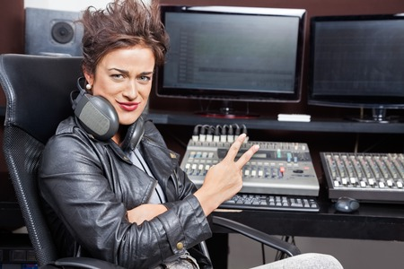 spiked hair: Portrait of female professional showing victory gesture at mixing table in recording studio