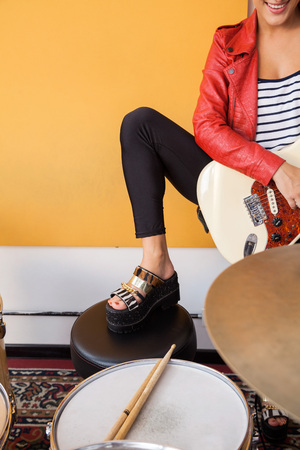 indie: Cropped image of female guitarist performing in recording studio Stock Photo