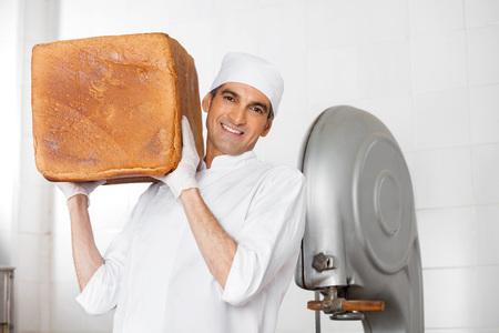 shoulder carrying: Portrait of confident mature male baker carrying big bread loaf on shoulder in bakery
