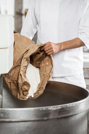 Midsection de boulanger mûre verser la farine en pétrissant la machine à la boulangerie