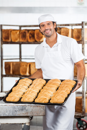baking tray: Portrait of smiling male baker showing breads in baking tray at bakery