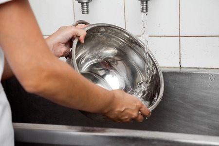 pan: Cropped image of female baker washing utensil at sink in bakery kitchen