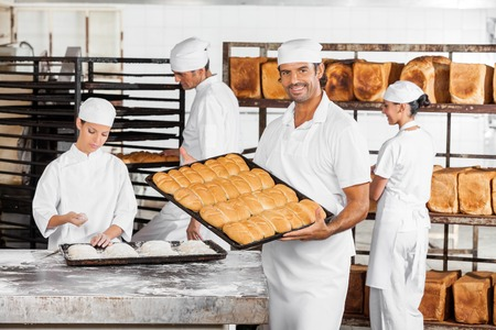 mid adult male: Portrait of mid adult male baker showing baked breads while coworkers working in bakery Stock Photo