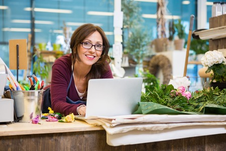 Portrait of mid adult female florist using laptop at counter in flower shop Stok Fotoğraf