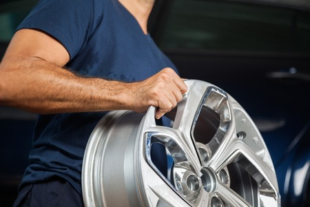 technician: Midsection of technician holding metallic alloy at repair shop