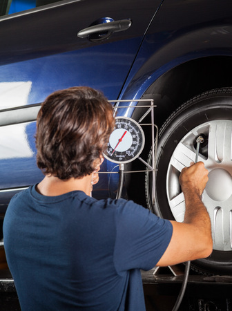 inflating: Rear view of male technician checking gauge while inflating car tire at garage