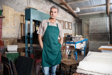 Portrait of confident mature worker standing with hands in pockets at factory Stock Photo