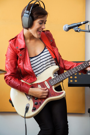 signer: Happy female signer playing guitar in recording studio