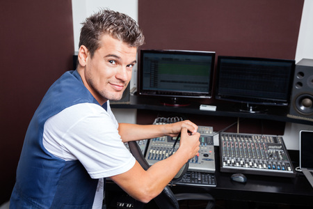masters of rock: Side view portrait of confident young man mixing audio in recording studio