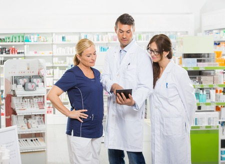 assistente femminile con tavoletta digitale con i farmacisti mentre in piedi in farmacia photo