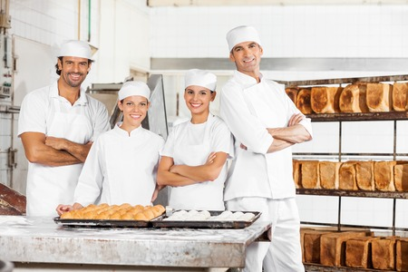 french bakery: Portrait of confident Bakers standing at table in bakery Stock Photo