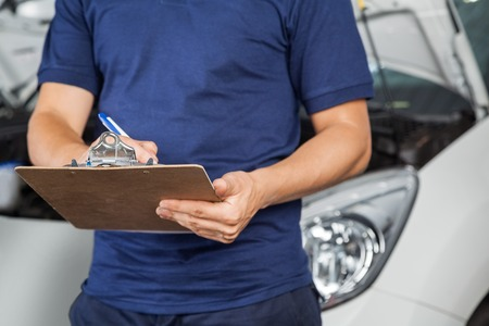 check list: Midsection of male mechanic writing on clipboard in garage