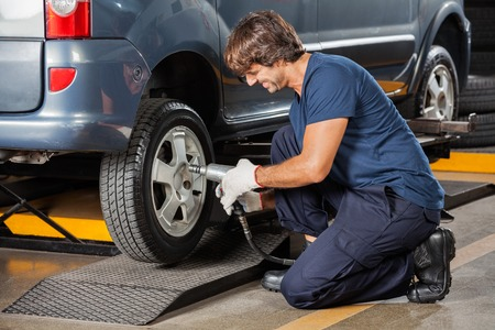 impact wrench: Male mechanic holding pneumatic wrench while fixing car tire at auto repair shop Stock Photo