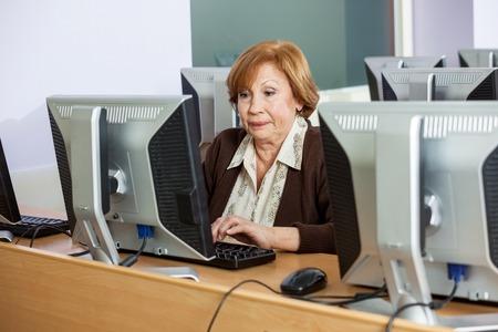 monitor de computadora: Senior femenino de los estudios utilizando PC de escritorio en clase del ordenador Foto de archivo