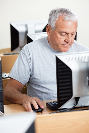 concentrated: Concentrated senior male student using computer at desk in classroom