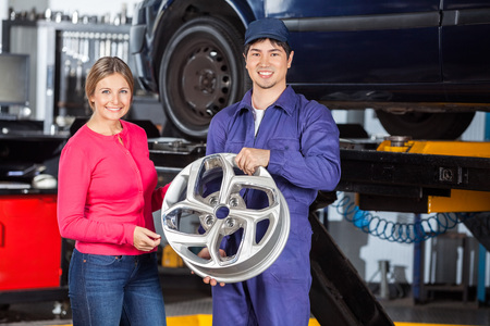 hubcap: Portrait of happy mechanic and female customer with hubcap at garage Stock Photo