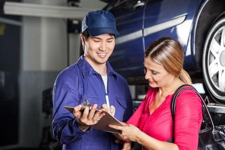 garage automobile: Homme m�canicien r�ception signe sur la facture du client f�minin dans le garage Banque d'images