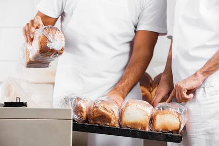 Midsection of male Bakers with packed bread loaves at counter in bakery