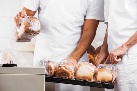 panadero: Sección media de hombres de Baker con barras de pan envasados ??en el contador en panadería Foto de archivo