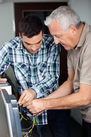 the elderly tutor: Male tutor and senior man fixing computer in classroom Stock Photo