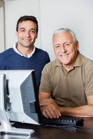the elderly tutor: Portrait of happy male teacher and senior man at computer desk in classroom Stock Photo